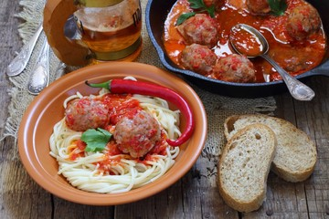 Meatballs in tomato sauce with a garnish from a spaghetti and be