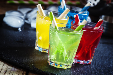 , yellow, red and green alcoholic cocktails with striped straws,