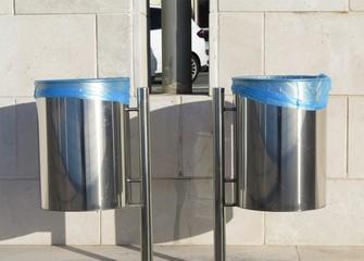 Two metal trash bins in urban street