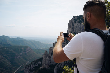 Young male tourist in white t-shirt takes photos with smart phone on peak of rock