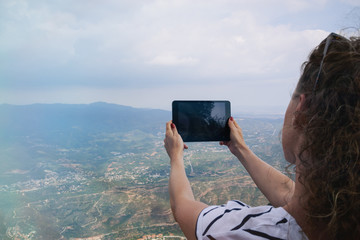 Female tourist takes photos with smart digital tablet on peak of rock