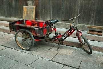 Red tricycle parked in a deserted street of Fenghuang