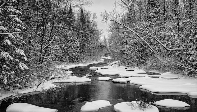 Teal river banks covered in snow in northwest Wisconsin.