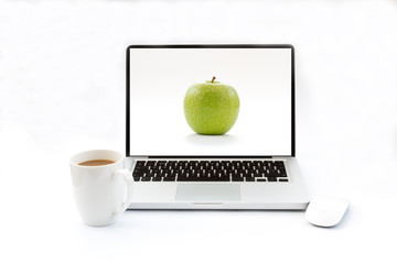 A laptop with an apple screen saver on an isolated white background. A white desk with a computer and hot drink to work at your desk.