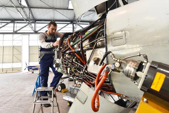 Flugzeugmechaniker repariert die Hydraulik am Triebwerk eines Flugzeuges // Aircraft mechanic repaired the hydraulics on the engine of an airplane