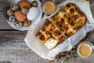 Easter hot cross buns with eggs rustic wood background