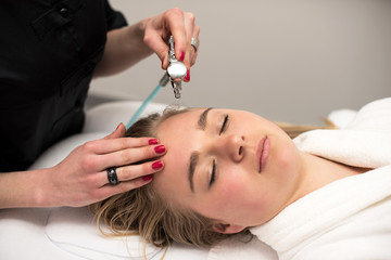 Young woman lying on massage table receiving face massage. Beaut