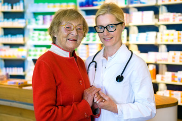 Happy doctor with female patient in pharmacy.
