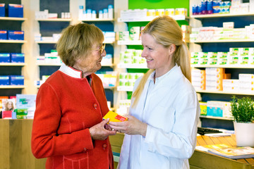 Friendly pharmacist giving customer prescription.