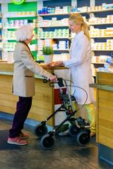 Elderly customer using walker with pharmacist.