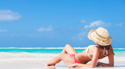 back view of long haired young woman in bikini and straw hat on tropical caribbean beach