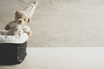 Toy teddy bear in a wicker basket on the table