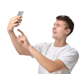 Young handsome man looking at smartphone and taking selfie