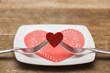 Fototapete - Pair of forks holding red heart during valentines day dinner