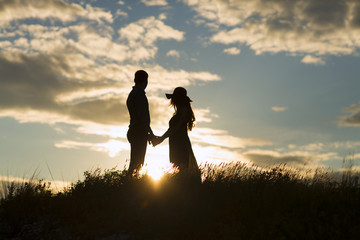 loving couple at sunset, silhouettes