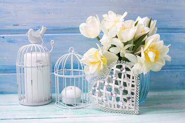 White daffodils and tulips, candles  and decorative  heart  on t