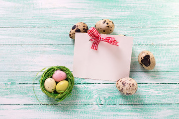 Decorative Easter eggs and empty tag on wooden background.