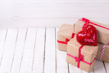 Festive gift boxes and red decorative heart  on white wooden bac