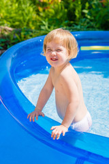 Funny little girl in blue inflatable swimming pool. Sunny summer day on countryside village.