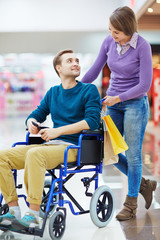 Pretty girl and her boyfriend in wheelchair shopping together