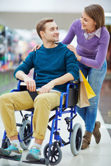 Pretty girl talking to her boyfriend in wheelchair during shopping