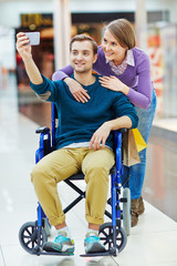 Pretty girl and her boyfriend in wheelchair making selfie during shopping