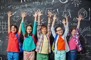 Ecstatic learners raising hands against blackboard