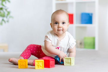 beautiful baby plays cubes on the floor and smiling