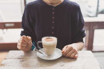 Young woman drinking latte in cafe