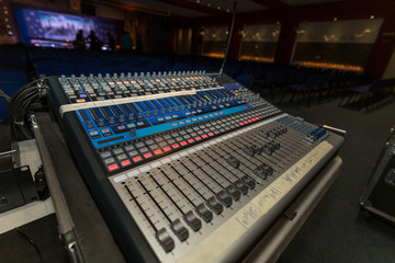 Professional music mixer console with faders and adjusting knobs in a theatre