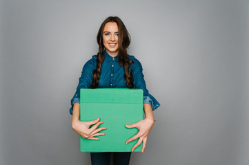 Attractive cute caucasian girl holding big square box in her hand ready to stock goods