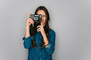 Portrait of cute teen girl texting emotional and making pictures to herself isolated on gray and studio background posing to the camera