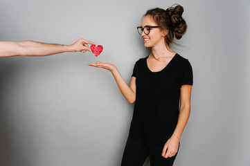 Portrait of cute teen girl with heart in her hand isolated on gray studio background posing to the camera