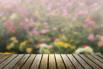 Wood table top with blur flower at garden