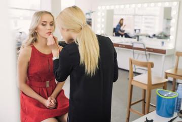 Expert stylist putting on lipstick on beautifill pretty girl