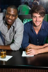 Portrait of two men having whiskey at bar counter
