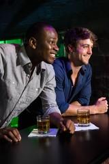 Two men having whiskey at bar counter