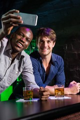 Two men taking a selfie on phone at bar counter