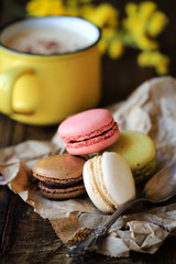 Delicious French macaroons on sack kraft paper with cappuccino coffee at the background on dar rustic wooden table