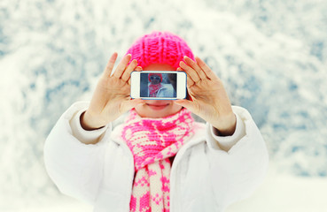 Hands woman makes self portrait on smartphone in winter snowy da
