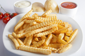 Portion of French fries (Crinkle-cut) deep fried, served on a white plate next to white bowls with mayonnaise and ketchup and fresh potato.