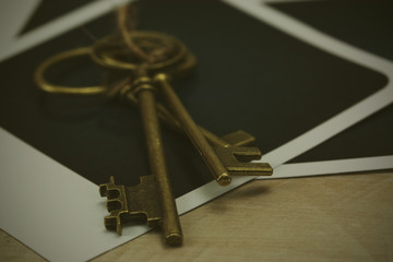 Old keys and photographs on a rustic background