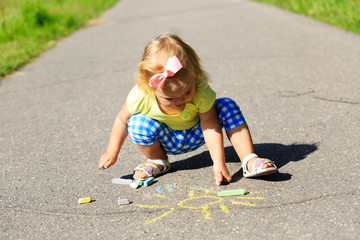 cute little girl drawing sun on a street
