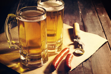 Beer in a glass on wooden background. Beer and beer snack.