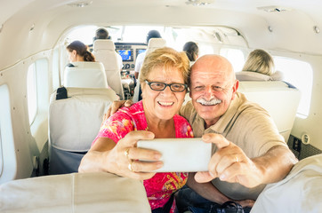 Senior happy couple taking selfie with mobile phone on board of plane  -  Smiling retired people having fun flying from Coron to Borakay  - Concept of elderly happiness on world wide travel