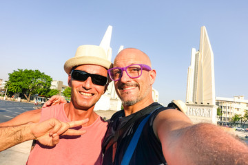 Happy couple of male friends taking selfie at Bangkok Democracy Monument - Cheerful tourists guys having fun with self photo in popular asian destination - Concept of joyful travel and old friendship