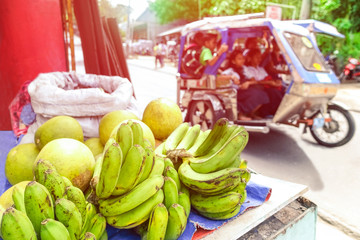 Close-up of bananas in traditional asian market at the roadside with blurred tricycle vehicle - Daily life scene with street fruit shop blur of students on popular  Philippines taxi - Focus on fruit
