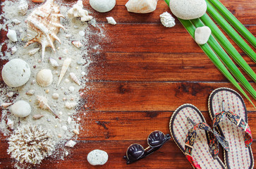 Marine items on wooden background. Sea objects - seashells, corals on wooden planks. Beach still life. View from above