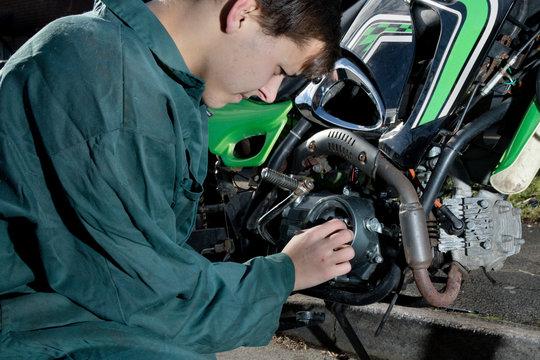 Teenage mechanic working on a motorbike