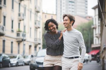 Knee figure of young handsome multiethnic couple having fun embr